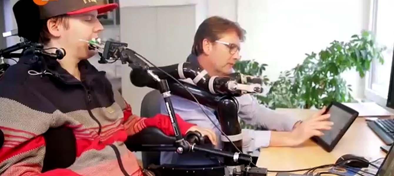 2 Personen sitzen nebeneinander am Schreibtisch. Einer von ihnen sitzt im Rollstuhl und hat einen Mundmaus vor sich aufgestellt, die andere Person arbeitet an einem Tablet PC.